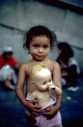 [Image: A child of a homeless family holds her doll, on the streets of Sao Paulo, Brazil, UN Photo #154976C]